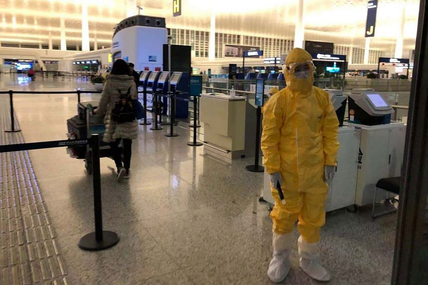 Staff wearing protective suits check passengers arriving to board a flight at Wuhan's international airport on Feb 7, 2020.
