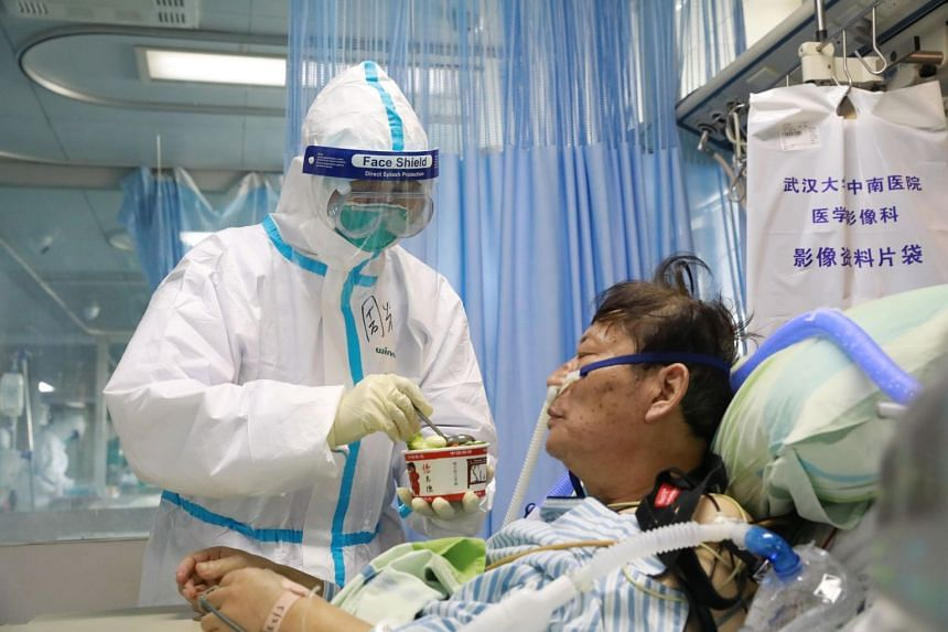 A nurse in a protective suit feeds a coronavirus patient in an isolated ward at Zhongnan Hospital of Wuhan University on Feb 8, 2020.