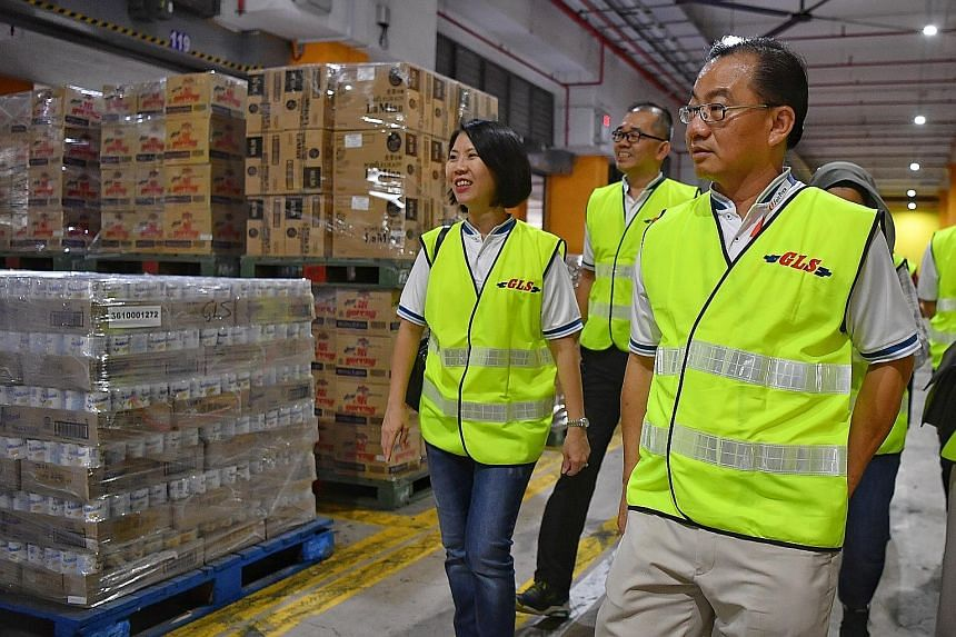 FairPrice group chief executive Seah Kian Peng (at right) visiting FairPrice's Benoi Distribution Centre yesterday. FairPrice has increased the volume of daily essentials being sent to the stores by three times. ST PHOTO: CHONG JUN LIANG