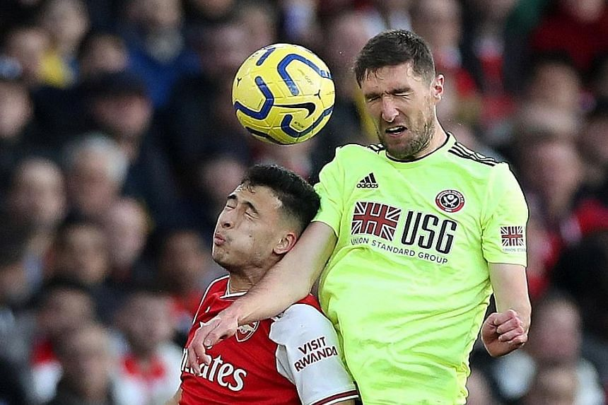 The successful switching of the versatile Chris Basham (outjumping Arsenal's Gabriel Martinelli) from midfield to defence shows that the 52-year-old English manager Chris Wilder has an eye for picking the right players. PHOTO: REUTERS