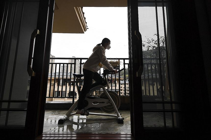 A student exercising on a stationary bike in Yunyang county, Chongqing. The county, in response to the new coronavirus outbreak in China, had called on students to minimise outdoor activities during the holidays. It suggested that parents guide their