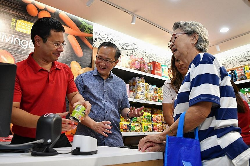 Minister for Social and Family Development Desmond Lee (in red) serving beneficiary Lai Siew Keng, 85, at the opening of the new store set up by charity Food from the Heart yesterday, accompanied by Mr Lim Biow Chuan, the MP for Mountbatten. ST PHOTO