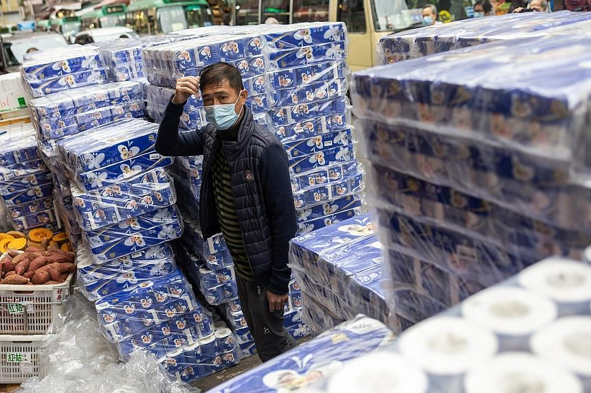 A man standing amid stacks of toilet paper outside a pharmacy in Hong Kong yesterday. Residents have been stockpiling essentials and toilet paper for fear of supply shortage.
