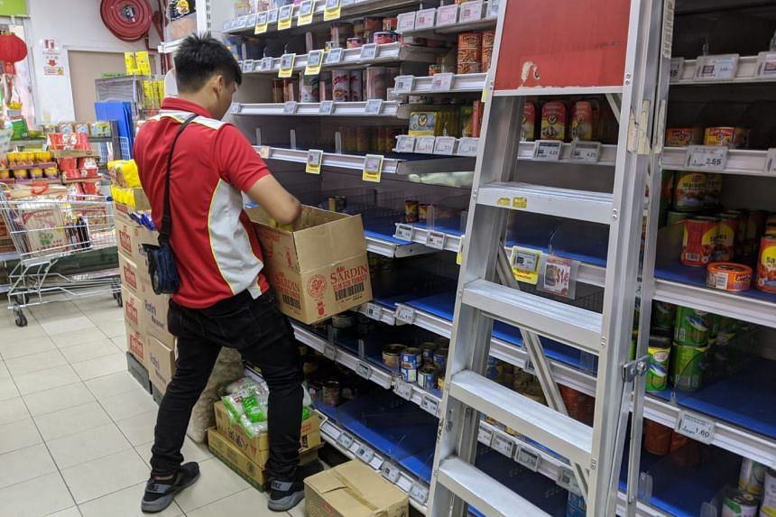 Staff at the Sheng Siong outlet in Superbowl Jurong restocking the shelves with canned food, on Feb 9, 2020.