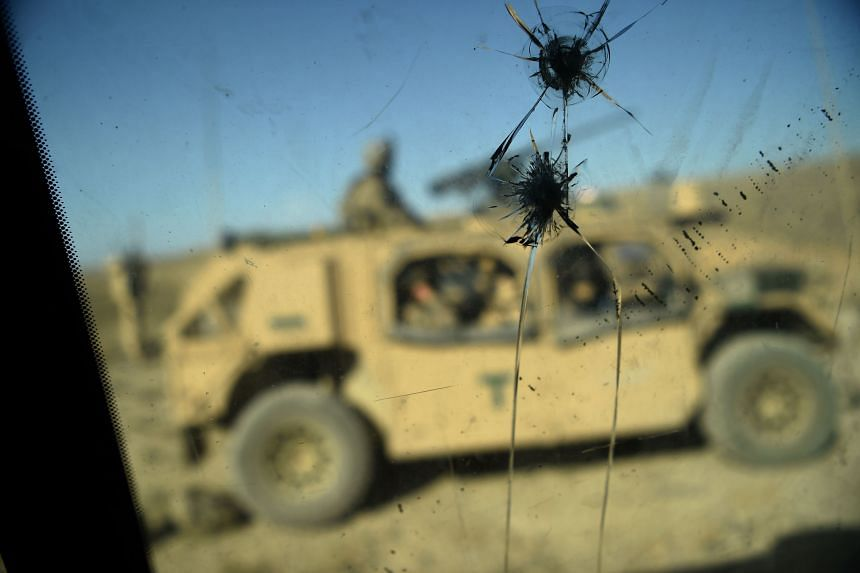 In a photo taken on July 7, 2018, US Army soldiers from NATO are seen through a cracked window of an armed vehicle in a checkpoint during a patrol against Islamic State militants at the Deh Bala district in the eastern province of Nangarhar Province.