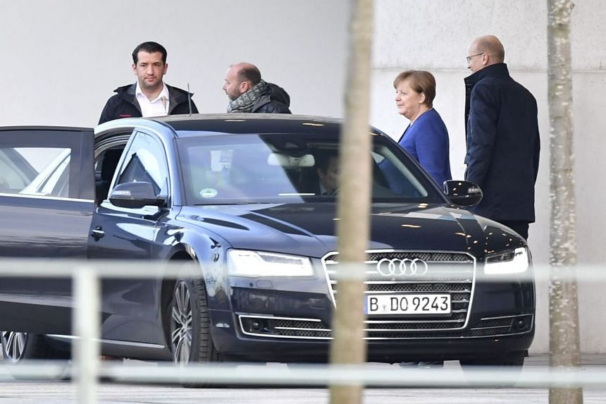 German Chancellor Angela Merkel (second right) and Ralph Brinkhaus, leader of the parliamentary group of the conservative CDU/CSU union, leave the Chancellery in Berlin on Feb 8, 2020.