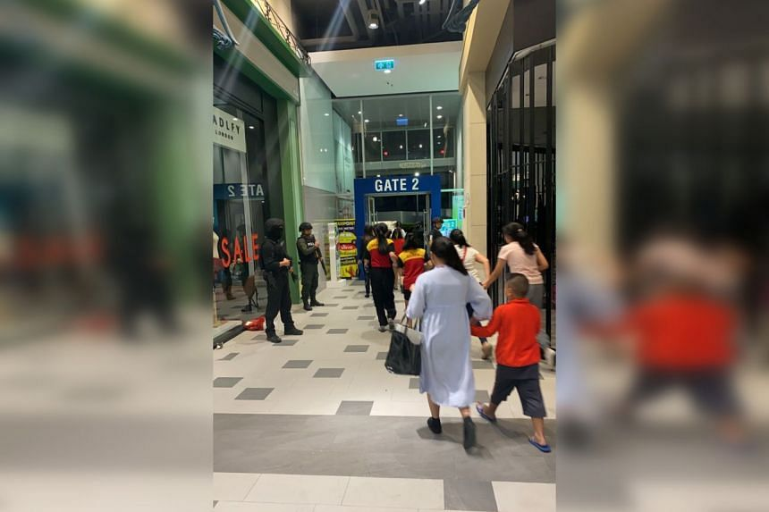 People are evacuated from a shopping mall by members of security forces after a shooting rampage in the city of Nakhon Ratchasima, Thailand.