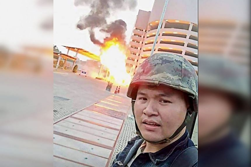 A screenshot from the Facebook livestream video of Thai soldier Jakrapanth Thomma shows him standing in front of a building on fire during an attack in the northeastern city of Nakhon Ratchasima on Feb 8, 2020.