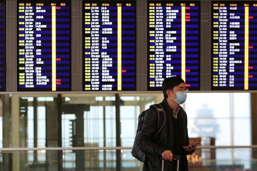 A passenger wears a protective mask as he walks through Hong Kong International Airport on Feb 7, 2020.