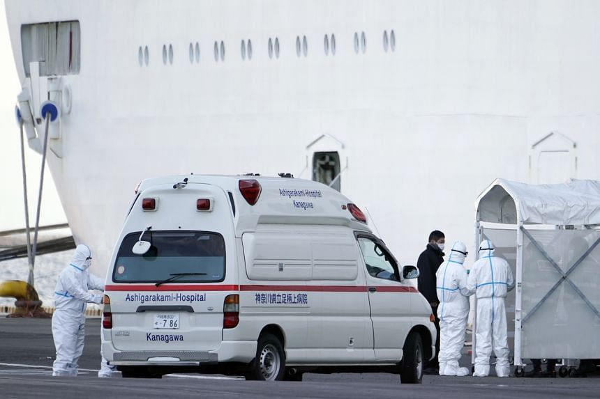 Medical personnel in protective gear stand next to ambulances at an entrance of the Diamond Princess cruise ship docked at the Daikoku Pier Cruise Terminal in Yokohama, south of Tokyo, on Feb 7, 2020.