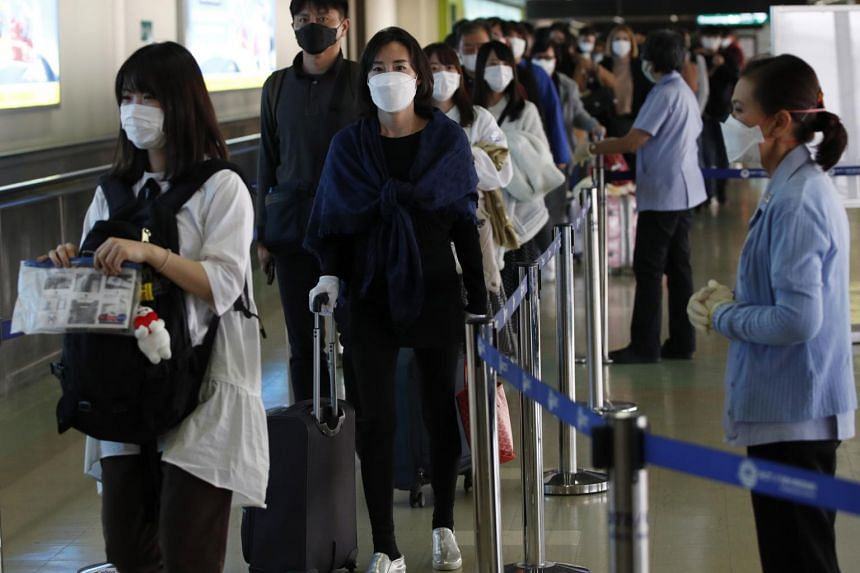 Thai health officials monitor the body temperature of arriving passengers at Don Mueang Airport in Bangkok on Feb 7, 2020.
