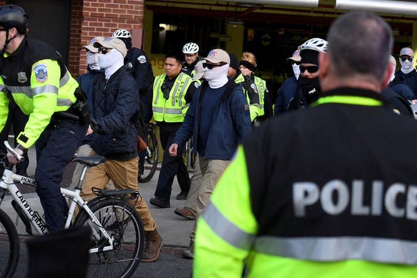 Police escort the last of about 150 masked members of the Patriot Front from a parking garage, after they peacefully ended a march near Capitol Hill in Washington on Feb 8, 2020.