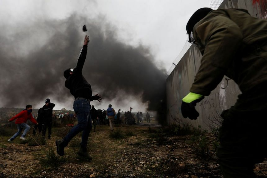 A Palestinian demonstrator hurling stones over a barrier at Israeli forces in protest against US President Donald Trump's Middle East plan in the Israeli-occupied West Bank on Friday. Palestine said yesterday that Israel had escalated the trade war