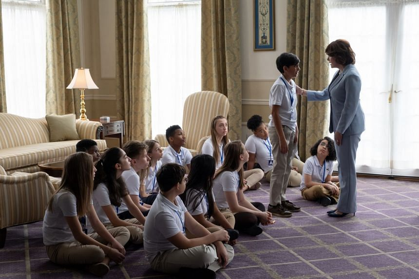 Another episode tells the story of a young Indian boy (played by Eshan Inamdar, standing) who seeks the help of First Lady Laura Bush (played by Sherilyn Fenn, far right) after his parents are deported and he is left to run the family motel in Utah.