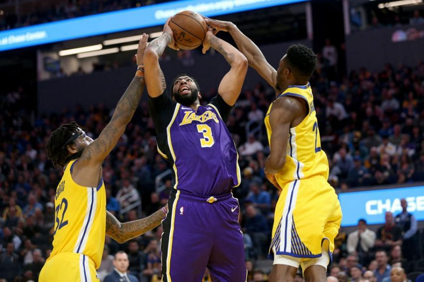 Los Angeles Lakers centre Anthony Davis (centre) going up for a shot against Golden State Warriors forwards Marquese Chriss (left) and Andrew Wiggins during their NBA match on Feb 8, 2020.