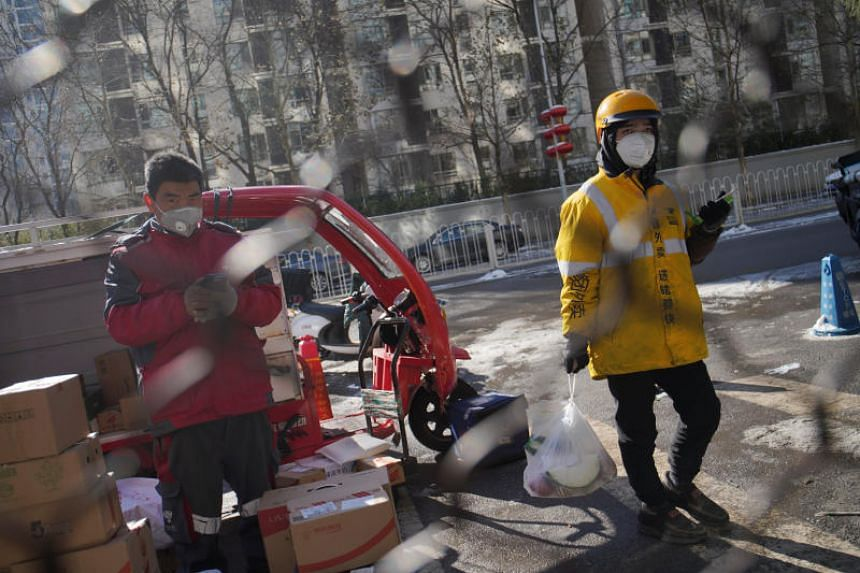 Delivery workers for JD.com (left) and Meituan making deliveries while wearking face masks, in Beijing on Feb 8, 2020.
