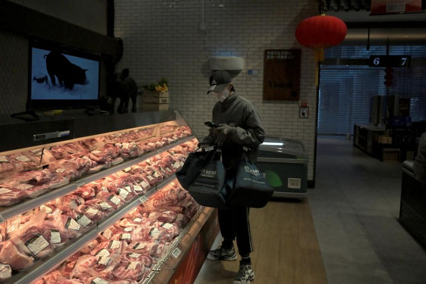 A staff member selecting pork items for online orders at JD.com's 7Fresh chain, in Yizhuang town, Beijing, on Feb 8, 2020.