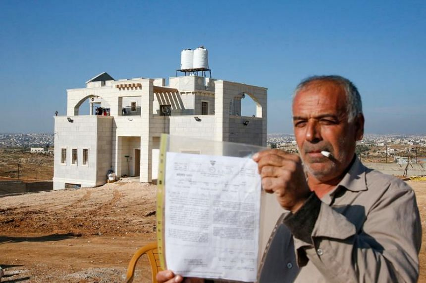 A Palestinian man carrying an Israeli court demolition order outside his house, in the village of Carmel, in the district of Hebron on Nov 21, 2019.
