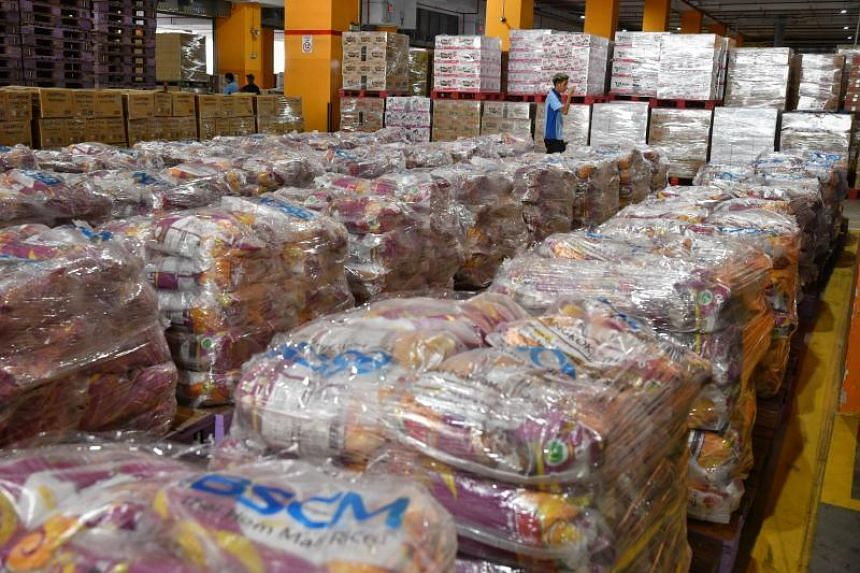 Sacks of rice, instant noodles and other food items stacked on pallets at FairPrice's Benoi Distribution Centre, on Feb 8, 2020.