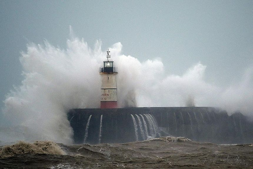 Waves crashing over the Newhaven Lighthouse on the south coast of Britain yesterday.