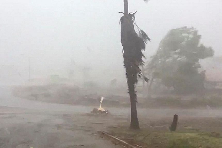 Trees swaying in Dampier, Western Australia, as Tropical Cyclone Damien made landfall in the state on Saturday, bringing winds of up to 200kmh. PHOTO: REUTERS A group of young men directing traffic through flood waters in Sydney, Australia, yesterday