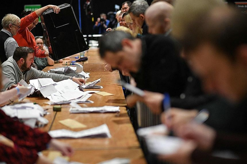 Vote counting under way for the Irish elections at the Dublin City count centre, in the RDS centre, in Ireland yesterday. An exit poll showed the nation's three biggest political parties in a dead heat.