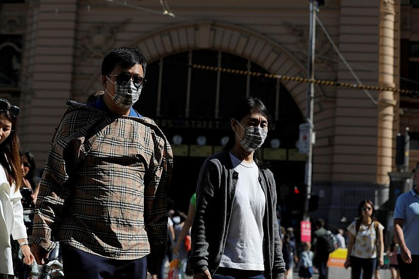 People wearing face masks at Flinders Street Station after cases of the coronavirus were confirmed in Melbourne. Australia's population of about 25 million includes more than 1.2 million people of Chinese heritage.