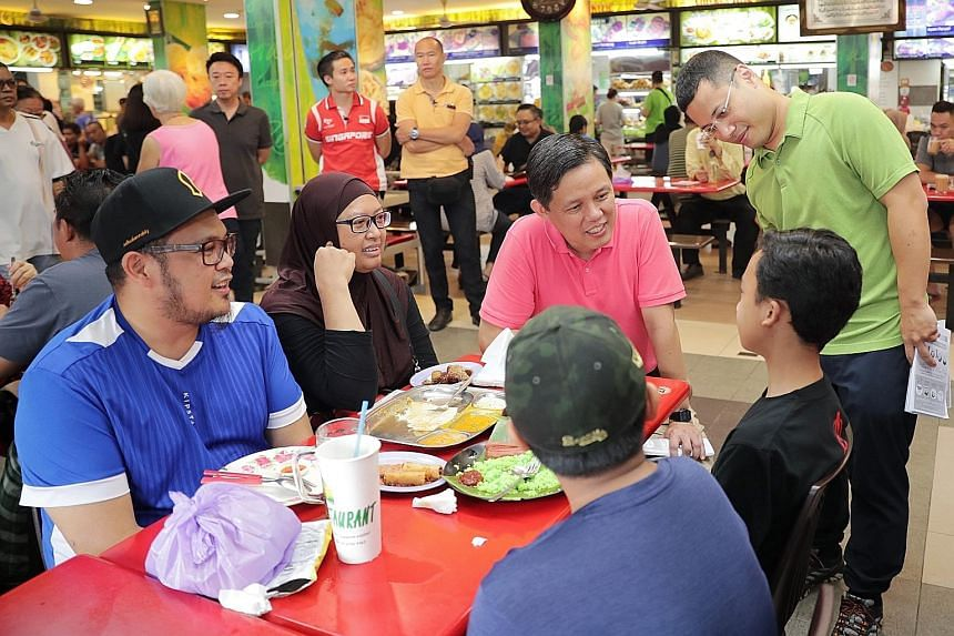 Trade and Industry Minister Chan Chun Sing (in pink) and Minister for Social and Family Development Desmond Lee (in green), who is also adviser to Jurong GRC grassroots organisations, speaking to residents during a ministerial community walkabout in