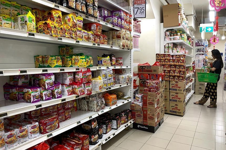 Shelves packed with instant noodles at a FairPrice outlet near Braddell Road yesterday. Singapore has over 40 fresh and instant noodle manufacturers, and some have upped supply. ST PHOTO: KUA CHEE SIONG