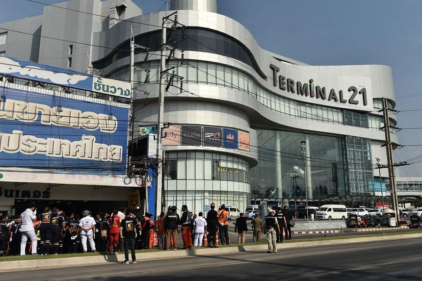People stand outside the Terminal 21 mall, where a mass shooting took place, in Nakhon Ratchasima, Thailand, on Feb 9, 2020.