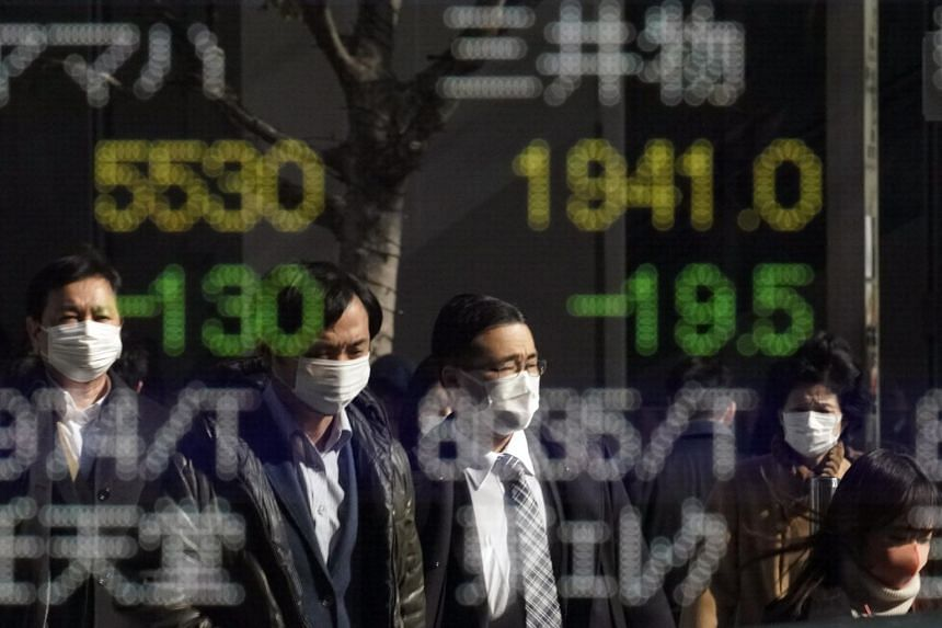 Pedestrians wearing masks reflected in a stock market indicator display board in Tokyo on Feb 3, 2020.