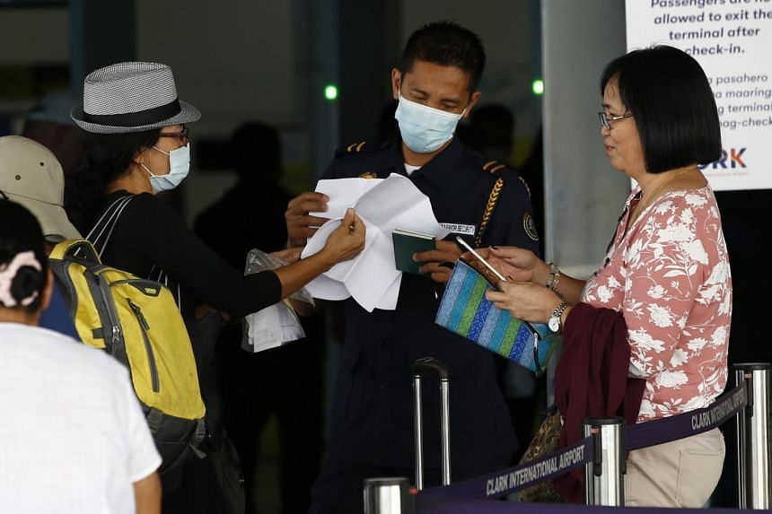 A security officer checks documents of travellers at the Clark International Airport in Mabalacat, Pampanga province, in Philippines, on Feb 8, 2020.