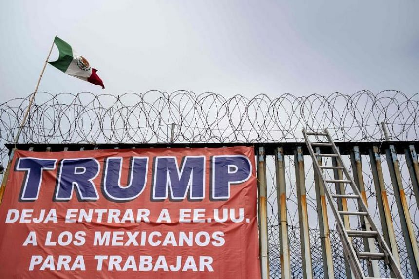 """A Mexican flag and a banner reading """"Trump, let Mexicans enter the US to work"""" are seen during a demonstration at the US-Mexico border in Playas de Tijuana, Baja California state, Mexico, on Feb 2, 2020."""