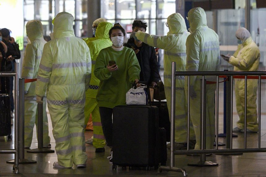 Chinese medical workers in protective clothing checking passengers' travel history at the Shanghai South railway station in the Chinese city yesterday, amid efforts to contain the coronavirus. With China playing a larger role in the global economy no