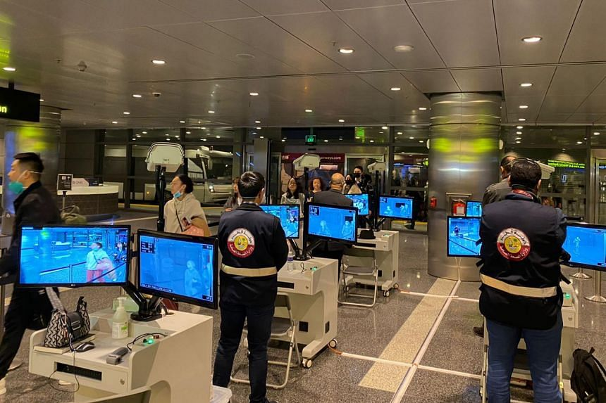 In a photo taken on Jan 24, 2020, travellers are seen walking past thermal scanners upon their arrival at Doha airport in the Qatari capital.