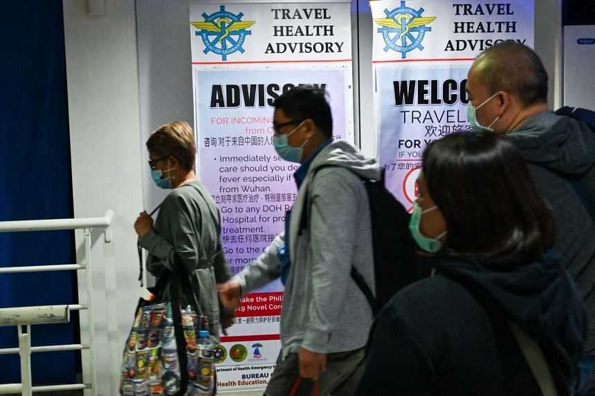Travellers with protective face masks walk past a travel health advisory sign upon arrival at the international airport in Manila, on Feb 5, 2020.