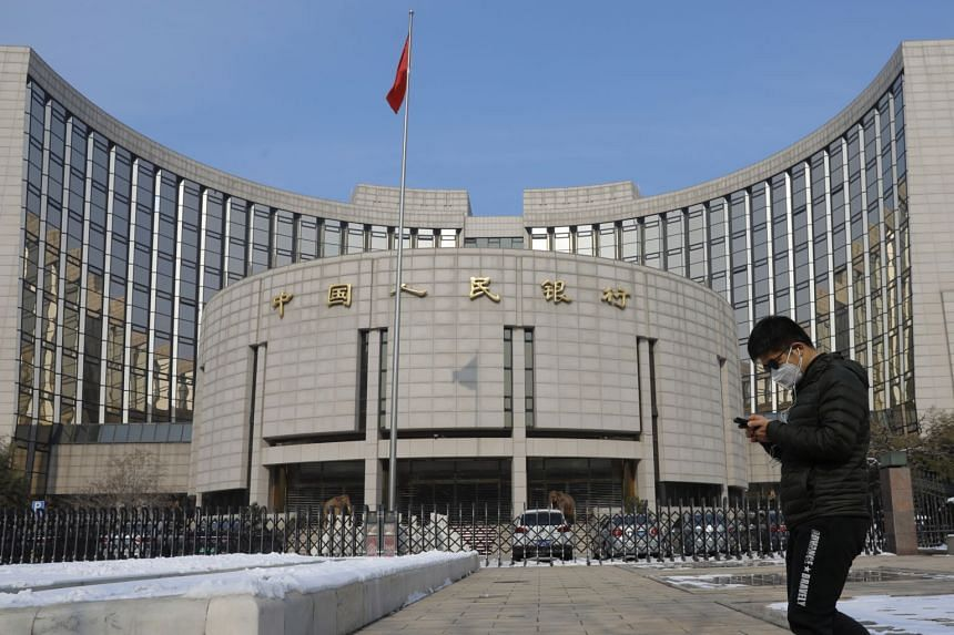 A man wearing a face mask walks past the headquarters of the People's Bank of China in Beijing, on Feb 7, 2020.