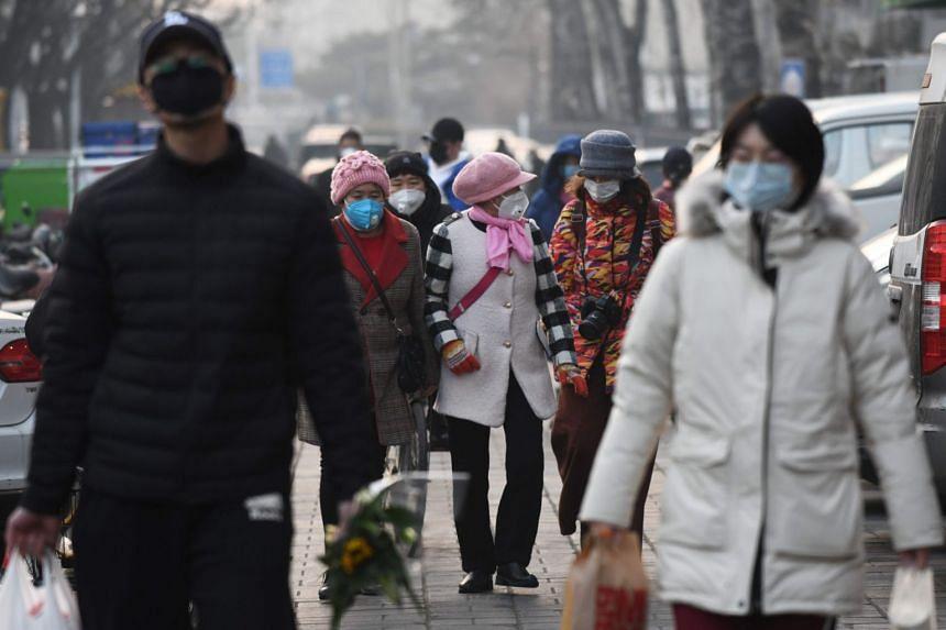 People wear protective face masks as they walk near a market in Beijing on Feb 9, 2020.