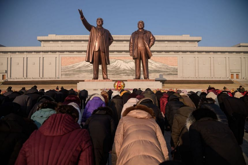 People bow before the statues of late North Korean leaders Kim Il Sung and Kim Jong Il on Mansu Hill, North Korea, on Feb 8, 2020.