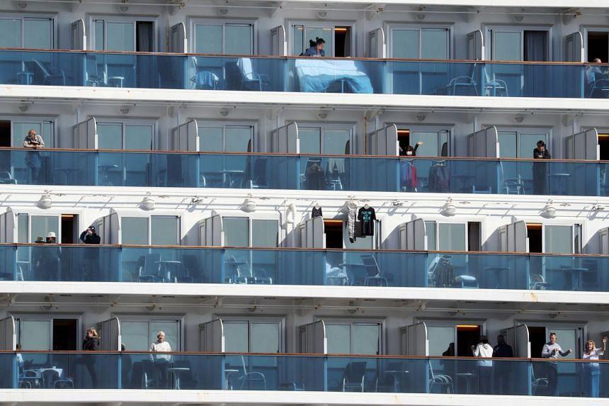Passengers of the Diamond Princess cruise ship gesturing from their balconies at the Daikoku Pier Cruise Terminal in Yokohama on Feb 9, 2020.