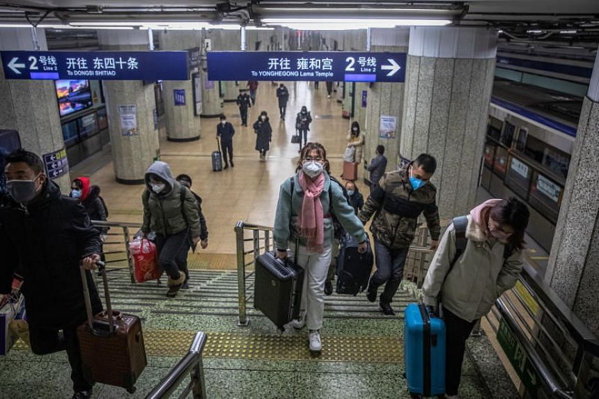 People wearing protective face masks while walking in a subway station in Beijing on Feb 10, 2020.