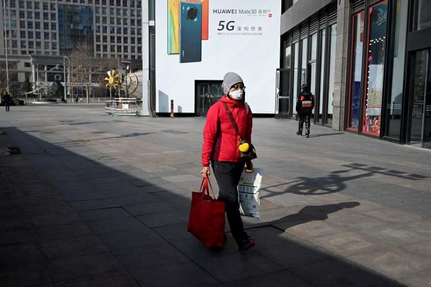 A woman wearing a face mask walks past a mall in Beijing on Feb 10, 2020.