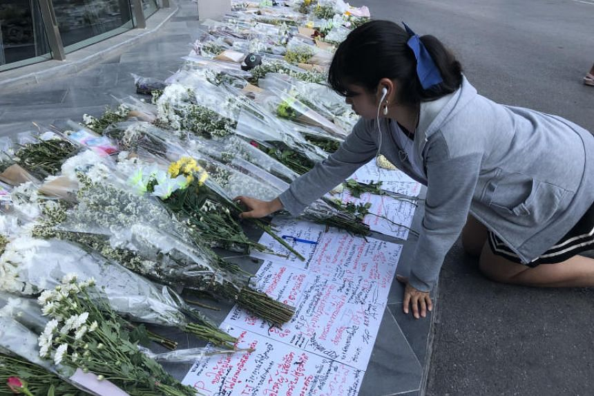 A woman laying flowers just outside Terminal 21 mall in Nakhon Ratchasima, Thailand, which came under siege by a gunman who killed 29 people on Feb 8, 2020.