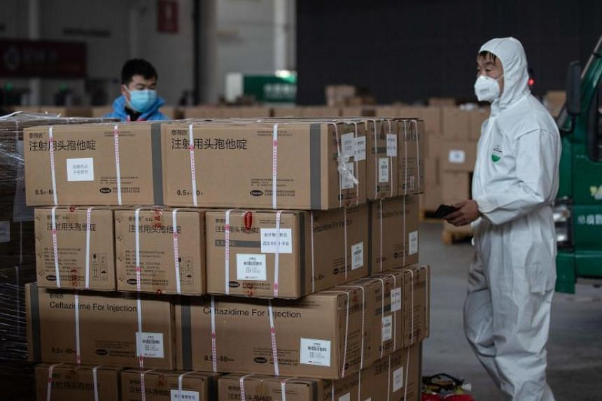 Staff and volunteers handle medical supplies at a warehouse which has been converted into a makeshift hospital in Wuhan on Feb 4, 2020.