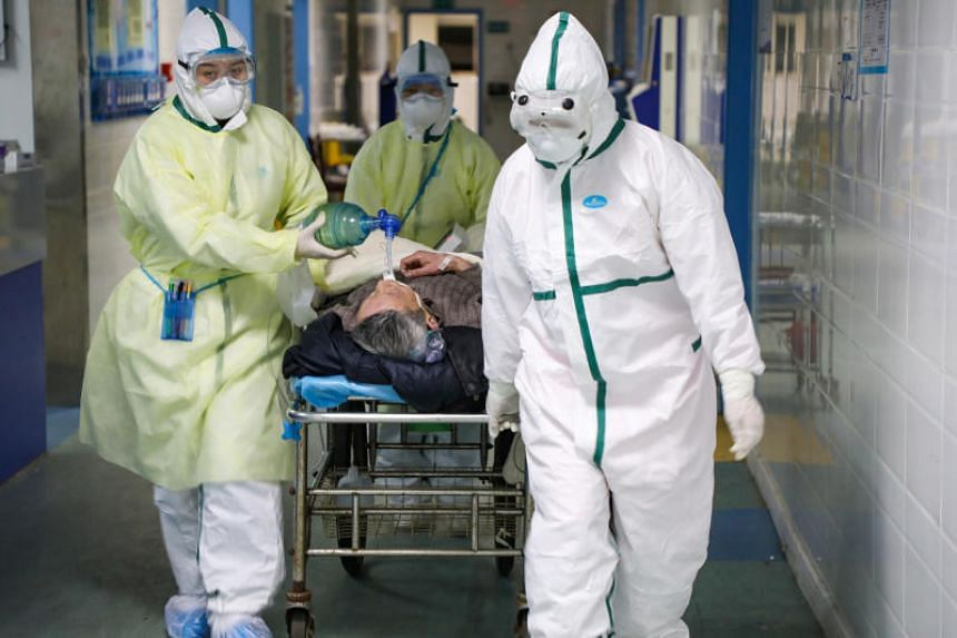 Medical workers moving a patient at an isolated ward of a hospital in Wuhan, China, on Feb 6, 2020.