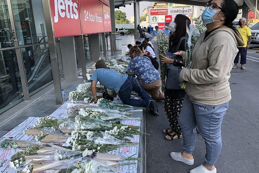 People laying bouquets of flowers yesterday outside the mall in Thailand where a shooting rampage took place on Saturday. ST PHOTO: HATHAI TECHAKITTERANUN
