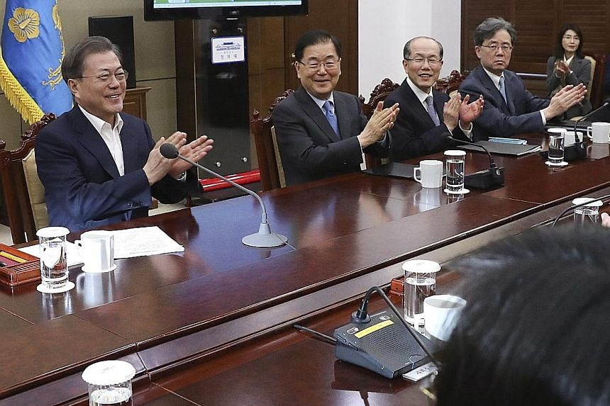 South Korean President Moon Jae-in (far left) and his top secretaries react after hearing that South Korean director Bong Joon-ho won four Academy Awards, prior to a meeting at the presidential office in Seoul. The news was also closely watched by So