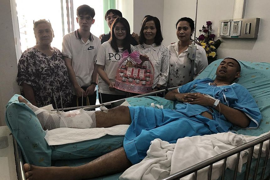 Police corporal Korakot Ampanngeun, who was shot in the leg by the gunman, is visited by his family at Maharat Hospital. Many people have flocked to major hospitals to donate blood. A woman laying a bouquet of flowers outside Terminal 21 mall in Nakh