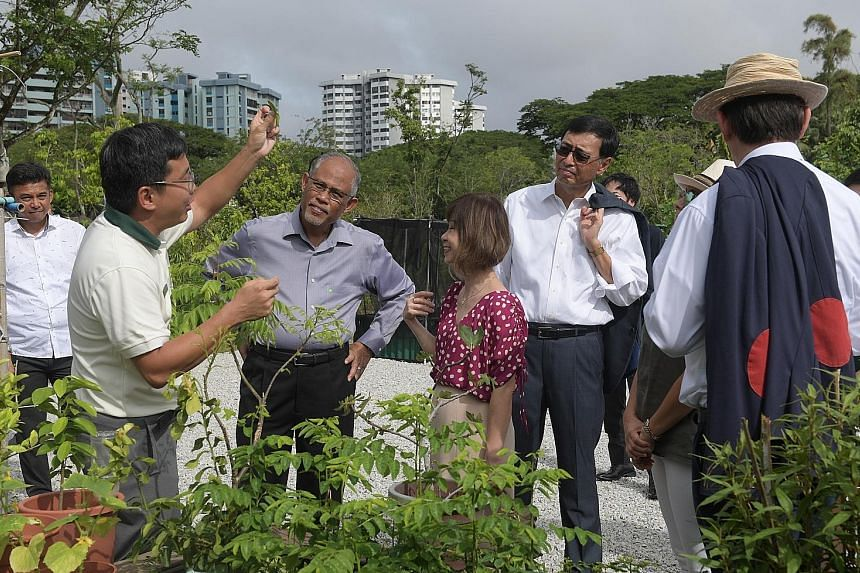 Dr Wilson Wong (at left), deputy director of Jurong Lake Gardens, speaking to Environment and Water Resources Minister Masagos Zulkifli, Senior Minister of State for the Environment and Water Resources Amy Khor and other guests on a tour of a communi
