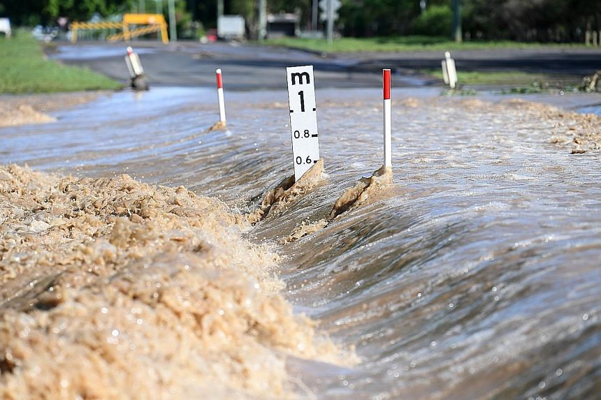 Floodwater gushing over a road in Australia's north-eastern Queensland state yesterday. While parched lands received a welcome drenching, the storms and heavy rain across the country's east coast over the weekend saw boulders falling on parked cars,